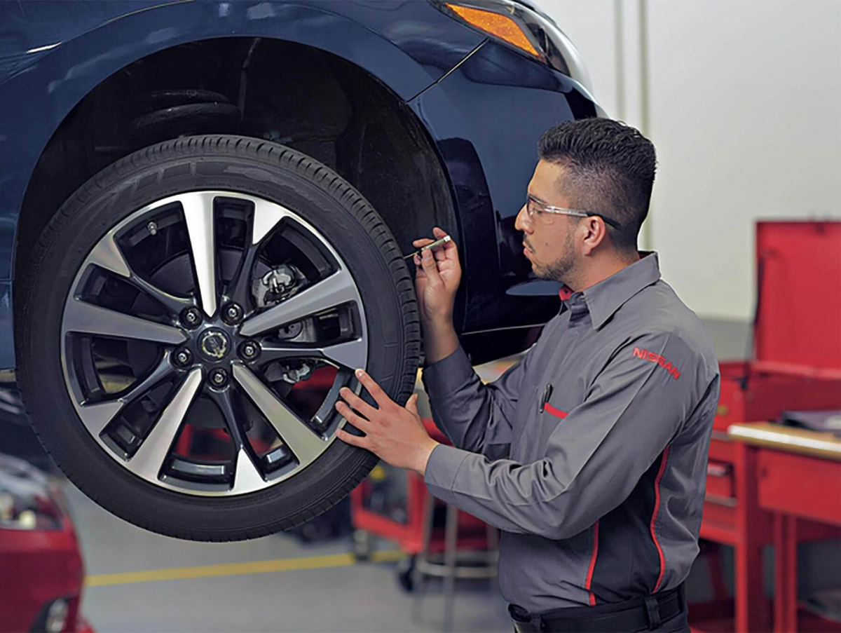 Nissan Service technician testing the tire treads on a vehicle